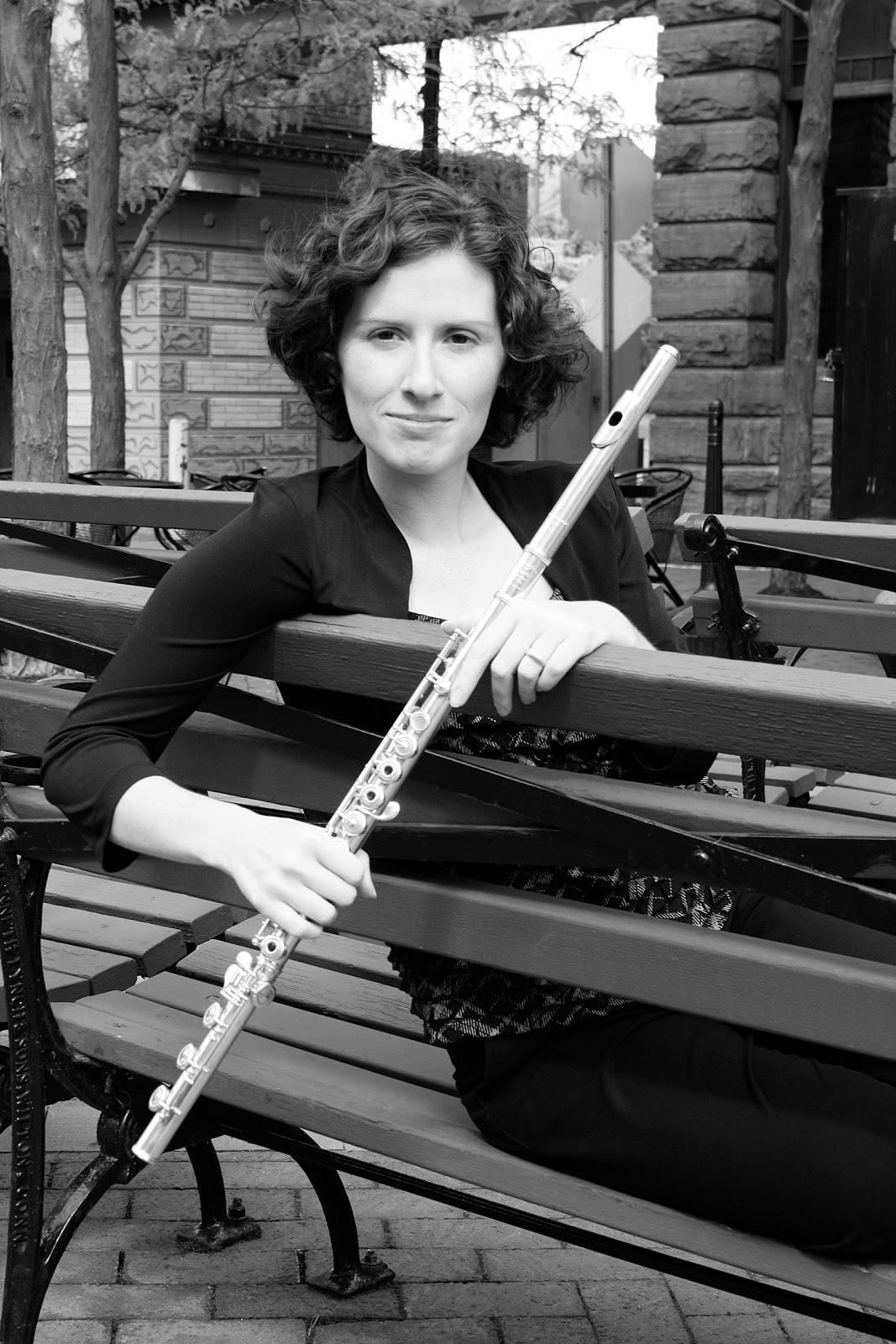 black & white: Alexis Del Palazzo, her flute, seated on bench w/ a smirk.